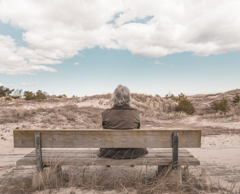 homem esperando no banco em deserto